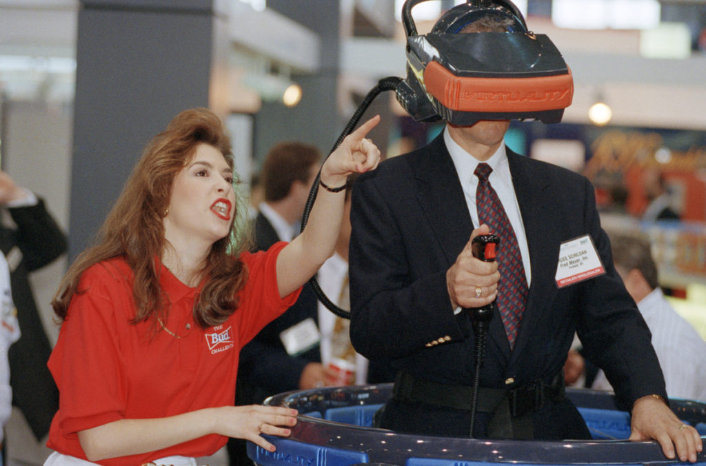Jamie Czerniak, left, shows Russ Schildan, of Portland, Ore., the Budweiser virtual reality mask at the Food Marketing Institute?s International Supermarket Industry Convention and Educational Expostion in Chicago on Sunday, May 9, 1993. The Anheuser-Busch company?s display featured a virtual reality game for three players. The convention runs through May 12. (AP Photo/Mike Fisher)